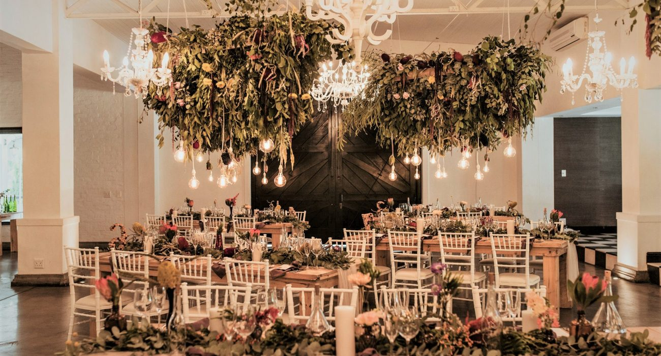 Wedding Decor Greenery And Flowers Hanging From Ceilings With Lighting