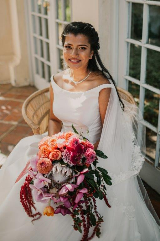 Iconic Beautiful Bride holding her gorgeous bridal bouquet from My Pretty Vintage Wedding Planners. Flowers include amaranth, protea, dahlia, orchid & tulip