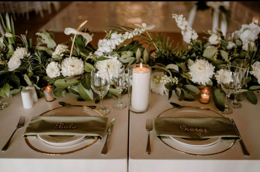 Wedding stationary guests names are laser cut out of wood and resting on olive green napkins and gold-trimmed plates.