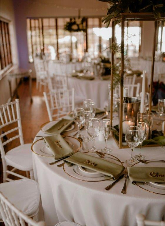guests names are laser cut out of wood and resting on olive green napkins and gold-trimmed plates.